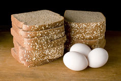 Bread eggs. Bread and eggs on wood background Royalty Free Stock Photography