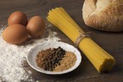 Bread, eggs and flour on a wooden table top stock photos