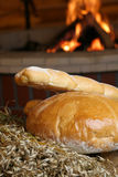 Bread with fireplace. Bread as traditional eatings on wood with fireplace in background Stock Images