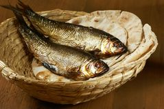 Bread and fish. Loaves of bread and two fishes in a basket Royalty Free Stock Photography