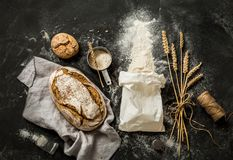 Bread, flour bag, wheat and measuring cup on black. Rustic bread, flour sprinkled from the white paper bag, measuring cup and ears of wheat - kitchen. Captured royalty free stock photography