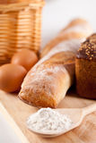 Bread, flour, eggs and kitchen utensil Stock Images