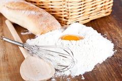 Bread, flour, eggs and kitchen utensil Stock Photos