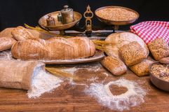 Bread and flour on a rustic wooden table royalty free stock image