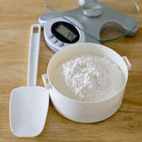 Bread flour in white bowl with rubber scraper and scale on wood Royalty Free Stock Images