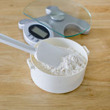 Bread flour in white bowl with rubber scraper and scale on wood Stock Photography