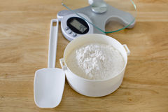 Bread flour in white bowl with rubber scraper and scale on wood Royalty Free Stock Image