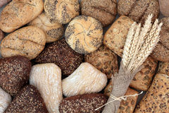 Bread Food of Life. Bread roll selection with wheat sheaths in hessian forming an abstract background Stock Photo