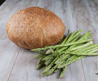 Bread and Fresh Asparagus with vegetables. On wooden background Stock Images