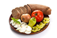 Bread and fresh vegetables on the plate isolated on wooden back Stock Images