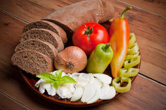 Bread and fresh vegetables on the plate isolated on wooden back Stock Photo