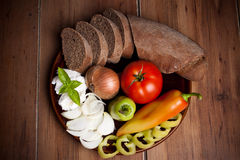 Bread and fresh vegetables on the plate isolated on wooden back Royalty Free Stock Photo