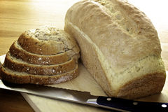 Bread. Freshly baked bread, some slices and a bread knife Royalty Free Stock Photo