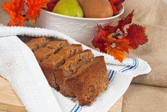 Bread and Fruit. Pear spice bread served in a clean dish towel. Bowl of pears in background with artificial autumn leaves Stock Photo