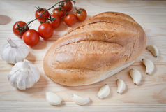Bread, garlic, cherry tomatoes. On a branch Stock Image