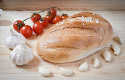 Bread, garlic, cherry tomatoes on a branch. Food abstract Stock Photo