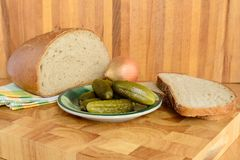 Bread and gherkin. On wooden board Stock Image