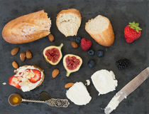 Bread, goat cheese, almond, honey and berries on a dark surface Royalty Free Stock Photos