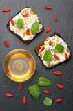 Bread with goat cheese, honey, goji berries and chia seeds. Delicious breakfast. top view Royalty Free Stock Photo