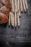 Bread golden wheat and rye ears on wooden board Royalty Free Stock Photography