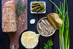 Bread with grains, pickled gherkins, lemon and sprats on a black Stock Photography