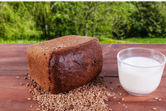 Bread and grains of wheat and a mug of milk. The background image of autumn leaves Royalty Free Stock Photography