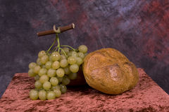 Bread and grapes. A loaf of bread and a bunch of grapes on a table Stock Photos