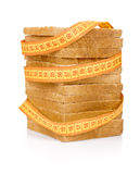 Bread grasped by measuring tape Stock Photography
