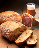 Bread,ham and beer. Bread and ham on a wooden table with a glas of beer in the background Stock Image