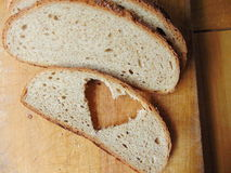 Bread with heart cut out of slice. In front Stock Image