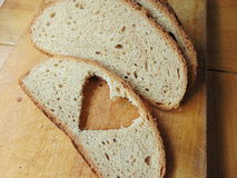 Bread with heart cut out of slice. In front royalty free stock photo