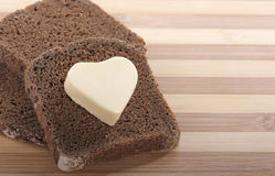 Bread and heart shaped butter Stock Photos