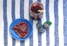 Bread with plum jam and some plums. Bread with homemade plum jam, a marmelade jar and some plums on a blue striped tablecloth stock photography