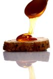 Bread with honey. Piece of bread with honey being poured from a wooden spoon royalty free stock images