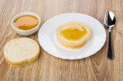Bread with honey in plate, teaspoon, bowl with honey. On wooden table Royalty Free Stock Photography