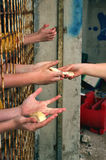 Bread for hungry hands. View of the hand that gives hungry children in prison bread. Aptraktna photos. The hand that gives bread to hungry hands behind other royalty free stock photos