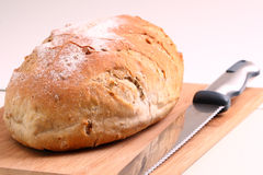 Loaf of bread and knife on a cutting board Stock Images