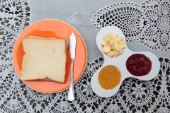 Bread with jam and butter. On a lace tablecloth. Royalty Free Stock Photos