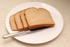 Bread with knife. Four slices of whole grain wheat bread on a plate with knife sitting on old counter Stock Photo