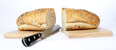 Bread Knife. A bread knife that has chopped bread and the board royalty free stock photography