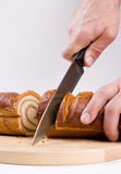 Bread and knife. A kitchen knife in a man's hand slicing a loaf of a long bread on a preparation board. Lots of crumbs on the board royalty free stock images