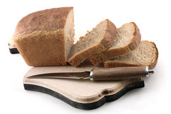 Bread and knife. Knife and the cut bread on a board on a white background Stock Photo