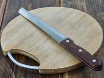 Bread knife. On the board Stock Photos