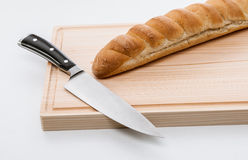 Bread and knife on chopping board Royalty Free Stock Images