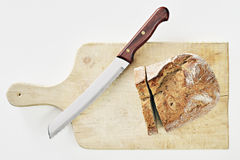 Bread and Knife. Rustic bread with a knife on a wooden cutting board Stock Images