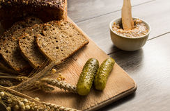 Bread lard and pickles on old wooden cutting board Stock Images