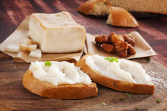Bread with lard spread. Bread with lard spread and pork scratchings on wooden cutting board on wooden table. Culinary meat eating. Traditional british snacks Stock Photos