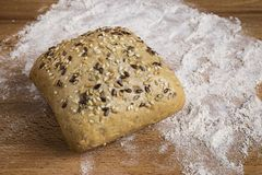 Bread with linseed, oats and sesame seeds. Next to some ingredients on a wooden table royalty free stock image