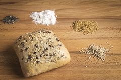 Bread with linseed, oats and sesame seeds. Next to some ingredients on a wooden table stock photo