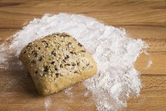 Bread with linseed, oats and sesame seeds. Next to some ingredients on a wooden table royalty free stock images